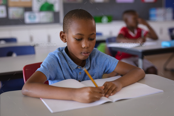 African american boy studying while sitting on his desk in the class at school - Stock Photo - Images