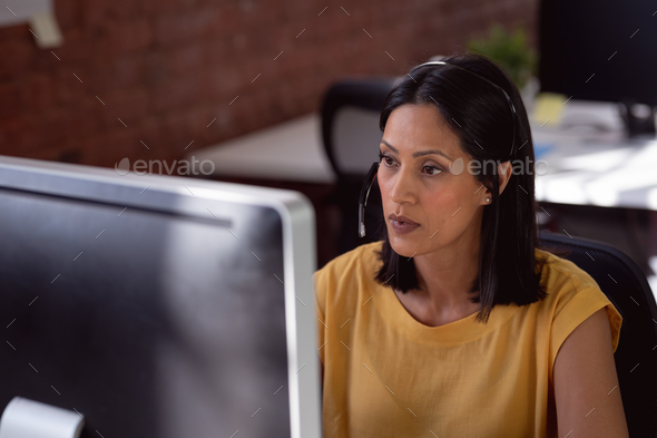 Caucasian businesswoman wearing phone headset sitting in office using computer and concentrating - Stock Photo - Images