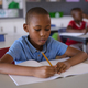 African american boy studying while sitting on his desk in the class at school - PhotoDune Item for Sale