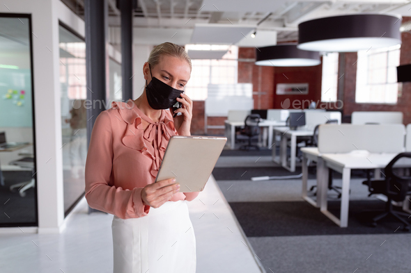 Caucasian businesswoman wearing face mask standing in office using tablet and talking on smartphone - Stock Photo - Images
