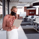 Caucasian businesswoman wearing face mask standing in office using tablet and talking on smartphone - PhotoDune Item for Sale
