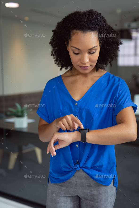 African american businesswoman checking smartwatch standing in office - Stock Photo - Images