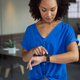 African american businesswoman checking smartwatch standing in office - PhotoDune Item for Sale