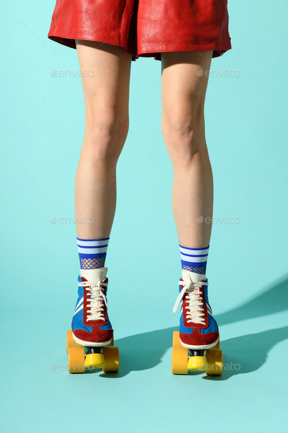 Legs of a slender sporty woman wearing multicolored roller skates - Stock Photo - Images