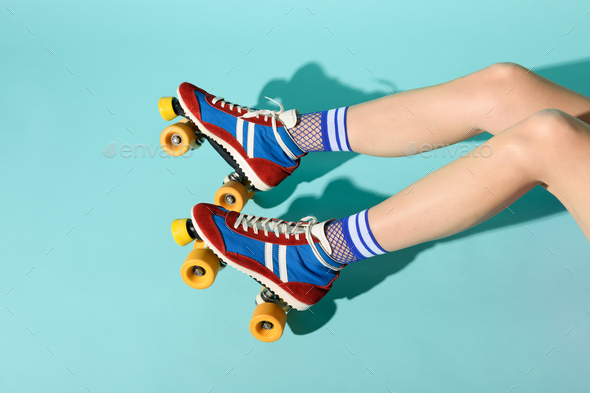 Young woman with thin skinny legs wearing colorful roller skates - Stock Photo - Images