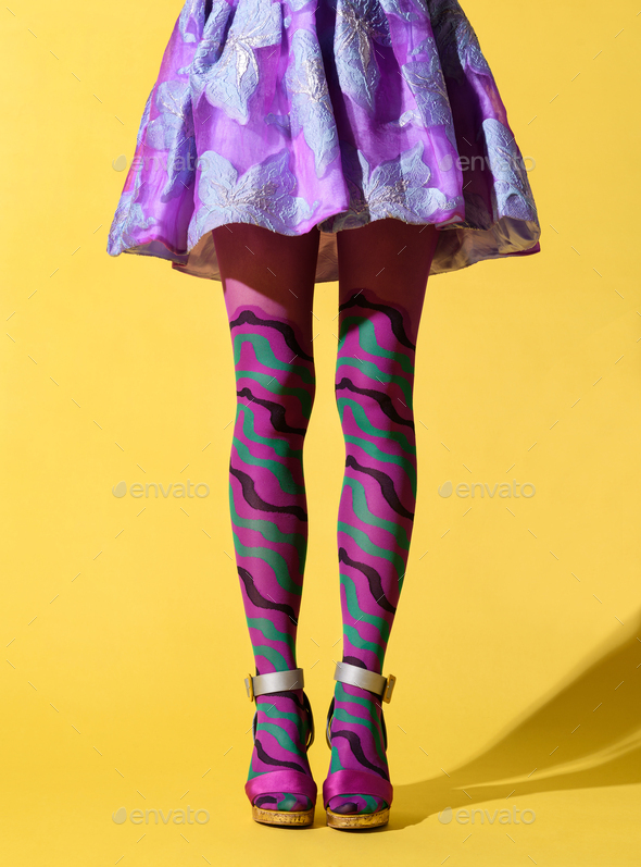 Skinny female legs with patterned purple collant - Stock Photo - Images