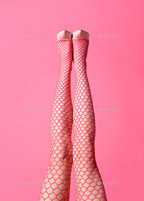 Sexy straight legs of a lady wearing pink fishnet stockings - Stock Photo - Images