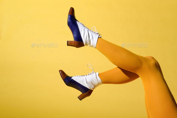 Sexy legs of a woman wearing mustard colored stockings - Stock Photo - Images