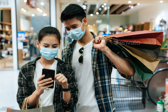 Young couple in mask holding multiple shopping paper bag - Stock Photo - Images