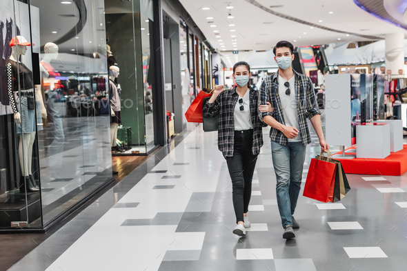 Young couple holding multiple shopping paper bag at mall - Stock Photo - Images