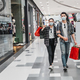 Young couple holding multiple shopping paper bag at mall - PhotoDune Item for Sale
