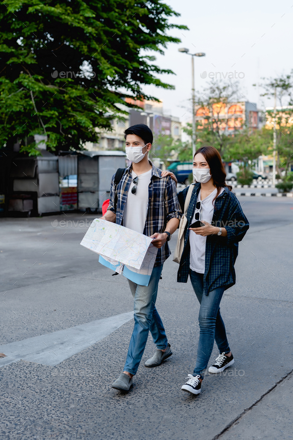 Young backpacker couple in mask checking location on paper map - Stock Photo - Images