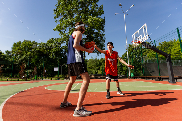 Two millennial sportsmen playing basketball match at outdoor playground, blank space - Stock Photo - Images