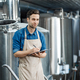 Serious man using brewing equipment at factory. Control of plant, collect data - PhotoDune Item for Sale
