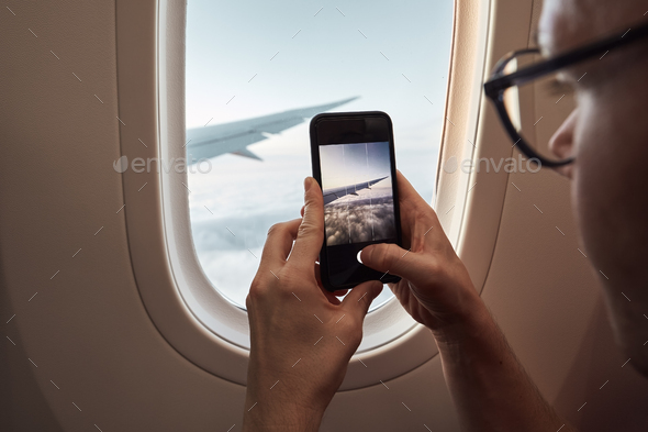 Passenger photographing through airplane window - Stock Photo - Images