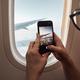 Passenger photographing through airplane window - PhotoDune Item for Sale