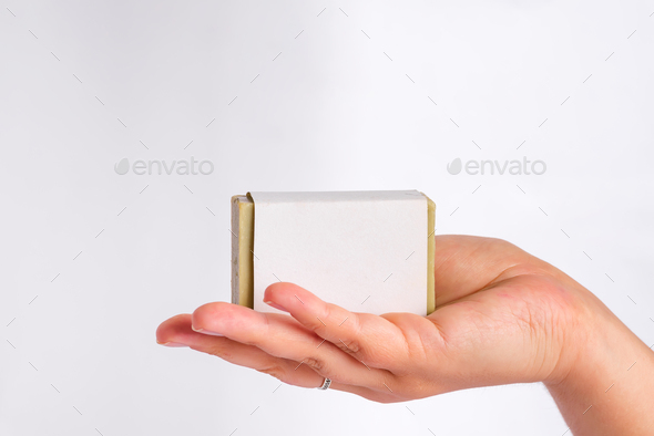 Woman's hands holding a bar of olive soap in package mockup - Stock Photo - Images