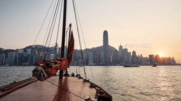 Traditional Junk boat against Hong Kong cityscape - Stock Photo - Images