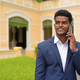 Happy African businessman outdoors wearing suit and talking on mobile phone while smiling - PhotoDune Item for Sale