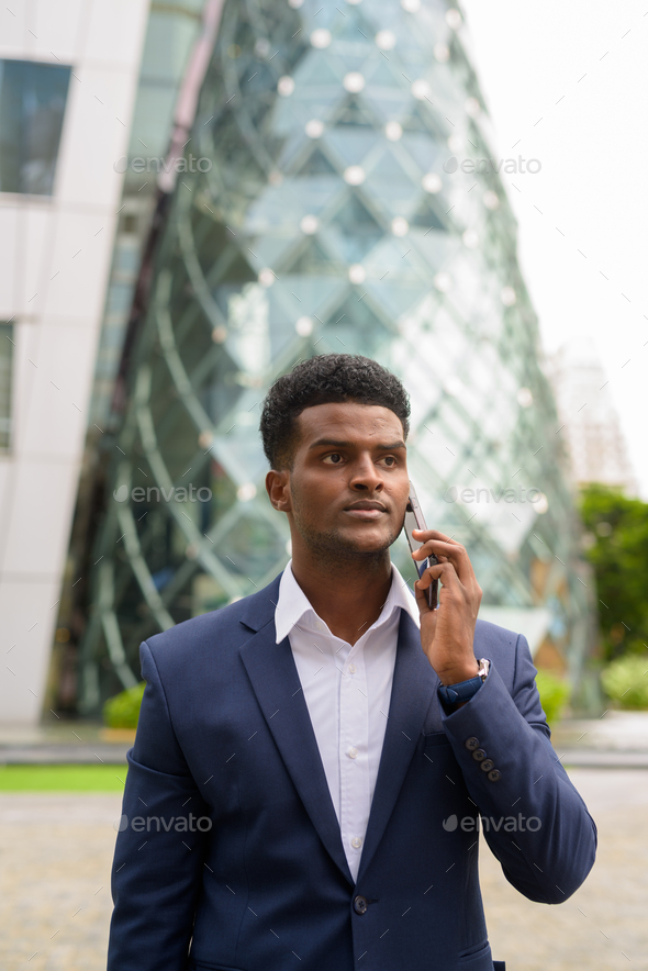 Portrait of African businessman outdoors in city talking on mobile phone - Stock Photo - Images