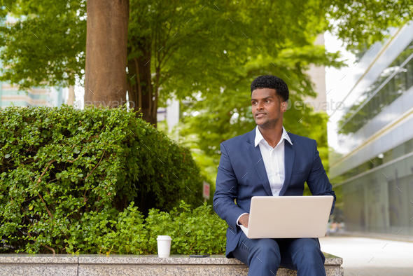 Portrait of African businessman using laptop computer - Stock Photo - Images