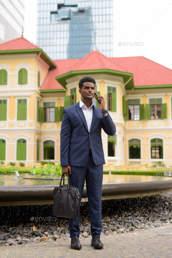 Full length shot of African businessman outdoors talking on mobile phone - Stock Photo - Images