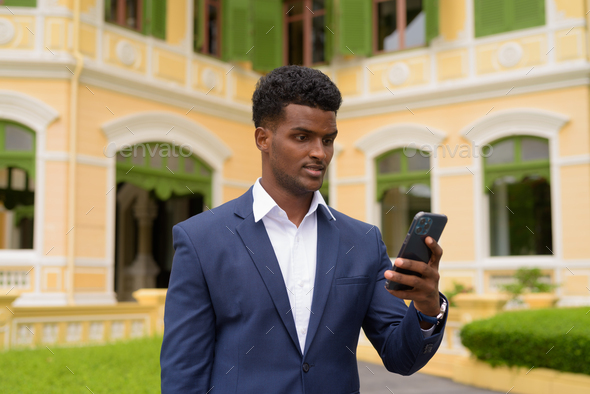 Portrait of African businessman outdoors wearing suit and using mobile phone - Stock Photo - Images