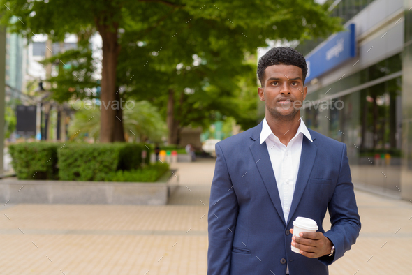 Portrait of African businessman holding take away coffee cup outdoors in city park - Stock Photo - Images