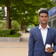 Portrait of African businessman holding take away coffee cup outdoors in city park - PhotoDune Item for Sale