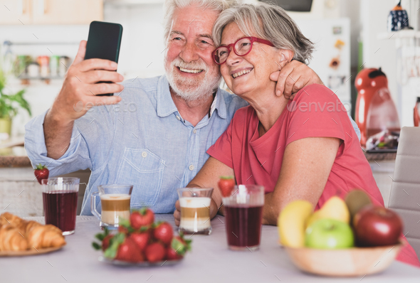 Beautiful couple smiling for a selfie, having breakfast at home. Senior people relaxed and happy - Stock Photo - Images