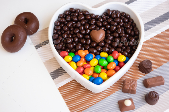 White heart-shaped bowl filled with brown and colorful chocolates, hazelnuts and almonds - Stock Photo - Images