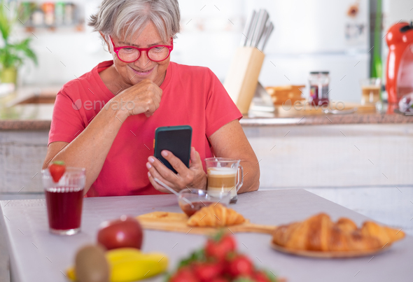 Attractive retired senior woman enjoying breakfast at home with croissant and cappuccino. - Stock Photo - Images