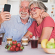 Beautiful couple smiling for a selfie, having breakfast at home. Senior people relaxed and happy - PhotoDune Item for Sale