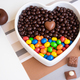 White heart-shaped bowl filled with brown and colorful chocolates, hazelnuts and almonds - PhotoDune Item for Sale