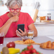 Attractive retired senior woman enjoying breakfast at home with croissant and cappuccino. - PhotoDune Item for Sale