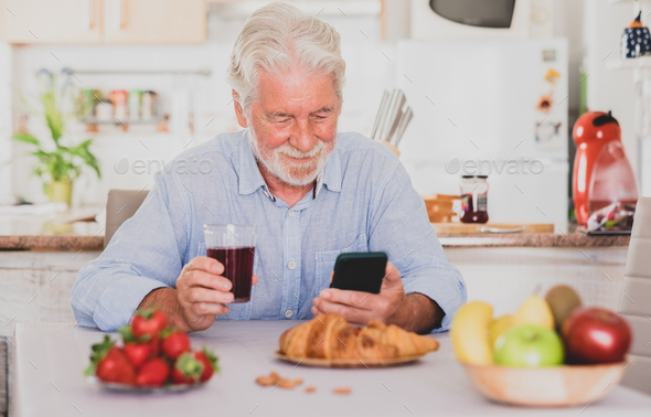 Beautiful senior man white hair having breakfast at home looking social media on smart phone. - Stock Photo - Images