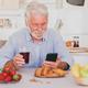 Beautiful senior man white hair having breakfast at home looking social media on smart phone. - PhotoDune Item for Sale