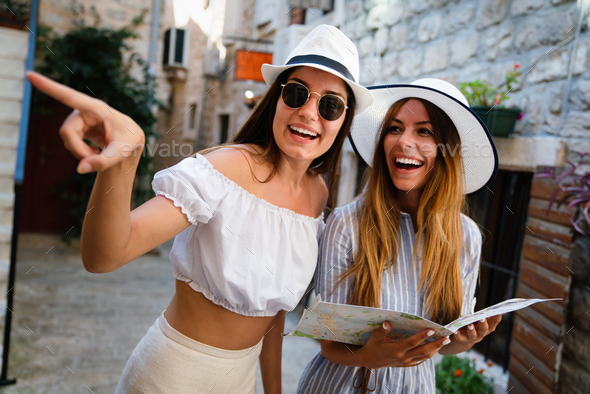 Happy young women with map in city. Travel tourist people fun concept - Stock Photo - Images