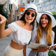 Happy young women with map in city. Travel tourist people fun concept - PhotoDune Item for Sale