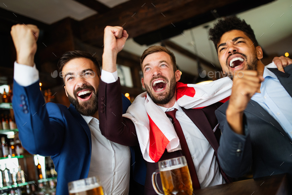 Group of friends at the pub watcing football game and drinking beer - Stock Photo - Images