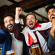 Group of friends at the pub watcing football game and drinking beer - PhotoDune Item for Sale