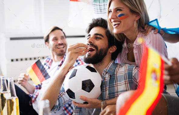 Cheerful and happy group of friends watching olympic games on tv - Stock Photo - Images