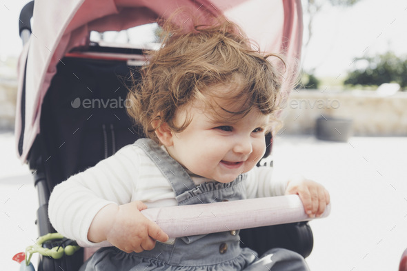 Beautiful little girl with curly hair sitting in her stroller - Stock Photo - Images
