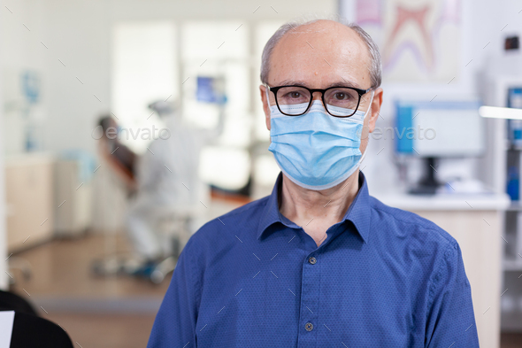 Portrait of elderly man in dental office looking on camera - Stock Photo - Images