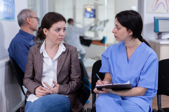 Nurse taking notes on clipboard discussing with patient in dental clinic - Stock Photo - Images