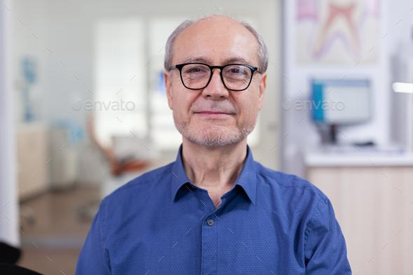 Senior man looking at camera in dental office wainting consultation - Stock Photo - Images