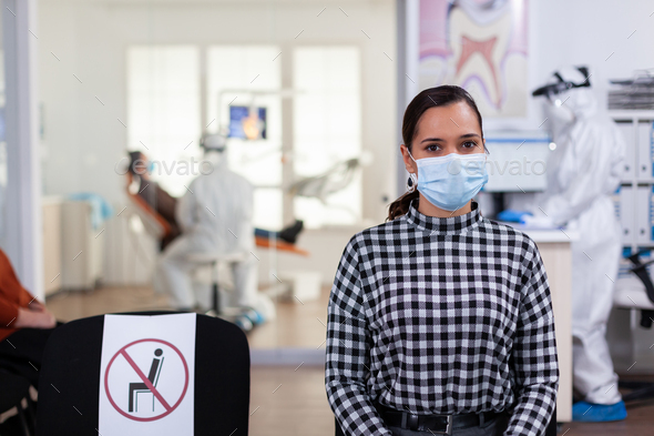 Portrait of woman in dental office looking on camera wearing face mask - Stock Photo - Images