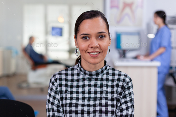 Portrait of smiling woman patient looking on camera sitting on chair - Stock Photo - Images