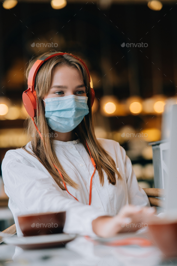 A girl sitting in a coffee shop with headphones. Coronavirus outbreak - Stock Photo - Images