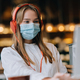 A girl sitting in a coffee shop with headphones. Coronavirus outbreak - PhotoDune Item for Sale